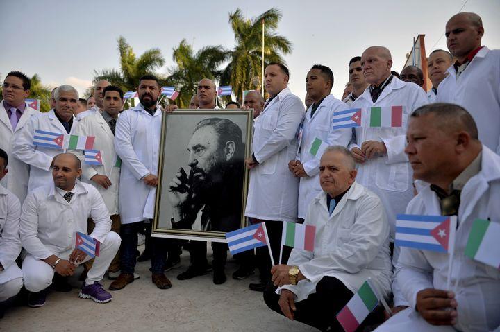 Les médecins et les infirmières de la Brigade médicale internationale Henry Reeve de Cuba posent avec un portrait de l'ancien président cubain Fidel Castro, alors qu'ils font leurs adieux, avant de se rendre en Italie durement touchée par la pandémie de coronavirus. Le 21 avril 2020. (YAMIL LAGE / AFP)