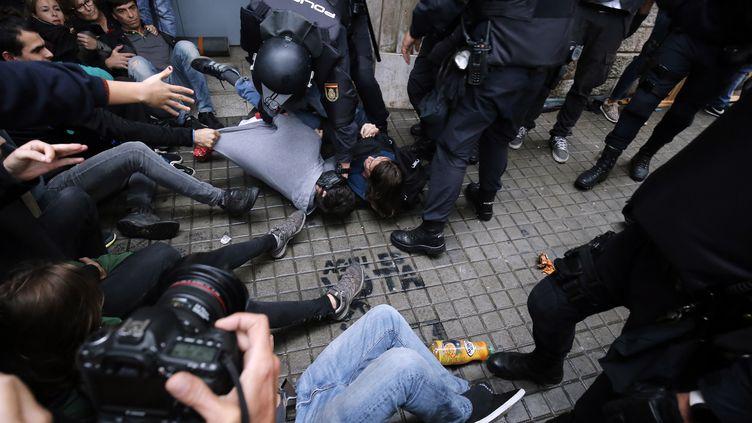 La police évacue de force des manifestants devant un bureau de vote de Barcelone (Espagne), lors du référendum d'autodétermination en Catalogne, le 1er octobre 2017. (PAU BARRENA / AFP)