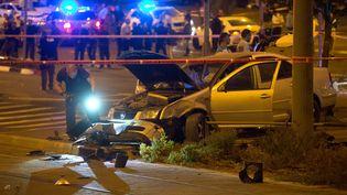 Des policiers israéliens examinent la voiture qui a foncé sur des piétons près d'une station de tramway à Jérusalem (Israël), faisant un mort et neuf blessés, le 22 octobre 2014. (MENAHEM KAHANA / AFP)