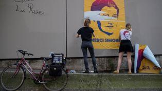 """Eléonore et Juliette, du collectif """"Merci Simone"""", devant une affiche de Simone Veil à Paris  (Thomas Samson / AFP)"""