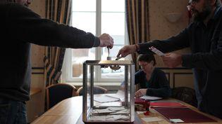 Un homme glisse son bulletin de vote dans l'urne, le 22 mars 2015 à Fontaine-sous-Jouy (Eure). (CHARLY TRIBALLEAU / AFP)