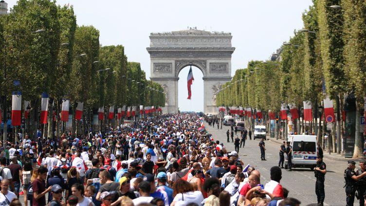 Les supporters français attendent l'arrivée des Bleus sur les Champs-Elysées, à Paris, le 16 juillet 2018. (ZAKARIA ABDELKAFI / AFP)