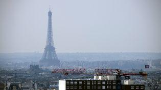La Tour Eiffel disparaît dans un brouillard dû à la pollution aux particules fines, le 27 mars 2014. (LIONEL BONAVENTURE / AFP)
