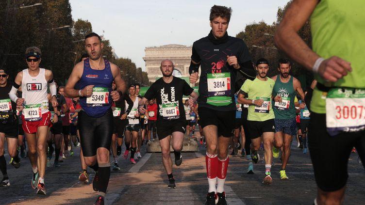 Les coureurs s'élancent sur les Champs-Élysées, le 17 octobre 2021. (GEOFFROY VAN DER HASSELT / AFP)