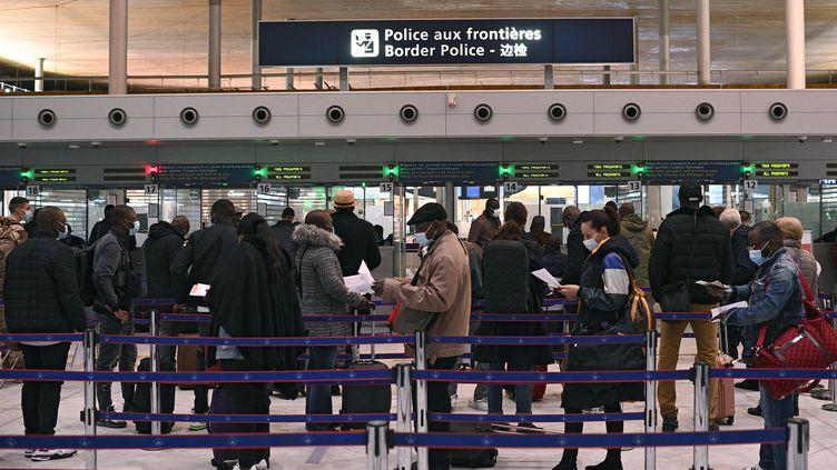 Des passagers attendent pour présenter leurs documents d'identité et leur attestation à la police aux frontières de l'aéroport de Roissy Charles-de-Gaulle, le 1er février 2021. (CHRISTOPHE ARCHAMBAULT / AFP)