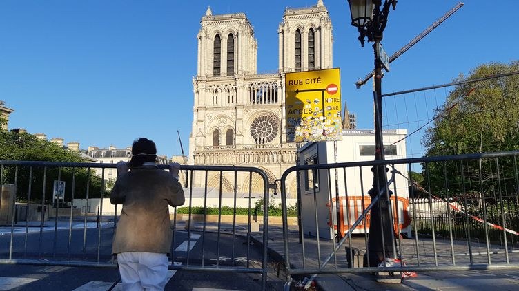 Fidèle priant devant la cathédrale Notre-Dame de Paris, le 15 avril, pendant que le bourdon résonne, un an après l'incendie de l'édifice. (BENJAMIN  ILLY / RADIOFRANCE)