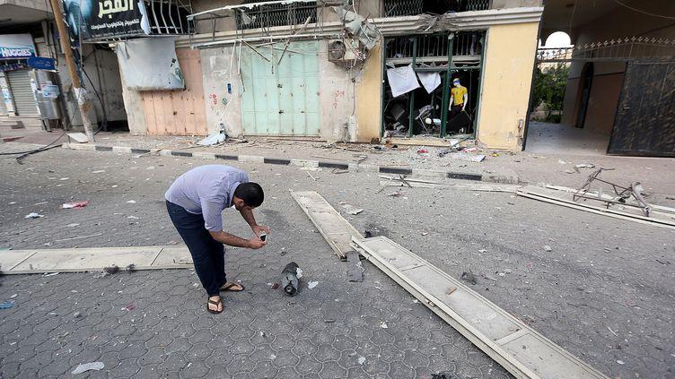 Un Palestinien inspecte les débris d'un obus israélien, le 17 juillet 2014 à Gaza. (MUSTAFA HASSONA / ANADOLU AGENCY)