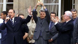 Le président de la République Jacques Chirac (g.), l'entraîneur de l'équipe de France de football (centre) et le Premier ministre Lionel Jospin (d.) avec le trophée de la Coupe du monde 1998 à l'Élysée, à l'issue du défilé du 14 juillet. (GABRIEL BOUYS / AFP)