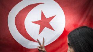 Une femme posant devant le drapeau tunisien, place de la République à Paris. Photo d'illustration. (XAVIER DE TORRES / MAXPPP)