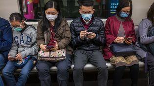 Des personnes portent des masques dans un train à Hong Kong, le 25 janvier 2020. (DALE DE LA REY / AFP)