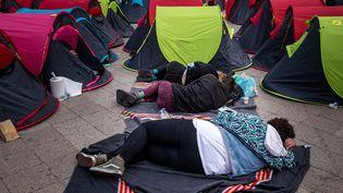 Des migrants sans-abri dorment sur le sol à côté de tentes installées la veille lors d'une action organisée par une association française devant l'Hôtel de Ville de Paris, le 25 juin 2021, pour souligner le sort des sans-abri dans le centre de Paris. (JOEL SAGET / AFP)