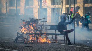 """Les chaises d'un restaurant en feu sur les Champs-Elysées, samedi 16 mars à Paris, où la manifestation des """"gilets jaunes"""" a dégénéré, avec des scènes de violences, d'affrontements avec les forces de l'odre, et de pillages. (ZAKARIA ABDELKAFI / AFP)"""