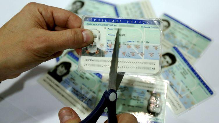 Un homme coupe en deux une pièce d'identité française avec une paire de ciseaux, le 22 janvier 2015 à Paris. (MAXPPP)