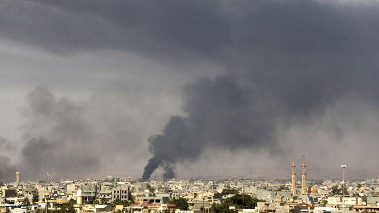 (Une fumée noire s'échappe d'un endroit où s'affrontent des milices libyennes © Reuters-Esam Al-Fetori)
