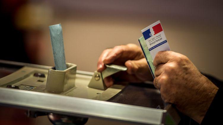 Un assesseur accepte le vote d'un électeur, dans un bureau de vote à Lille, le 6 décembre 2015. (PHILIPPE HUGUEN / AFP)