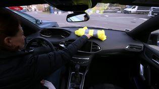 Une automobiliste pose un gilet jaune sur son tableau de bord, à Pont-de-Roide (Doubs), le 4 novembre 2018. (MAXPPP)