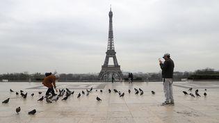 Malgré le confinement, les touristes prennent des photos sur la place du Trocadéro, à Paris, le 17 mars 2020. (LUDOVIC MARIN / AFP)