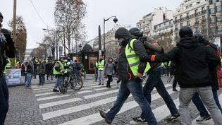 Des policiers arrêtent des manifestants sur les Champs-Elysées le 8 décembre 2018 à Paris. (MICHEL STOUPAK / NURPHOTO / AFP)