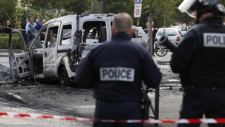 Des policiers devant une voiture de fonction brûlée à Viry-Chatillion (Essonne), le 8 octobre 2016. (THOMAS SAMSON / AFP)