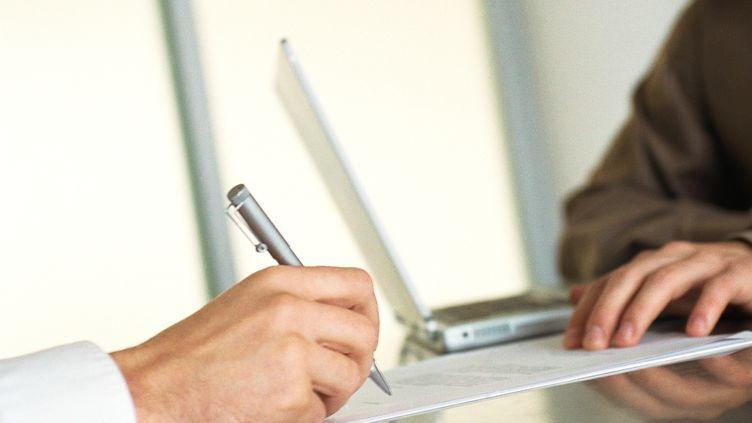 Un homme signe son contrat de travail à la fin de son entretien d'embauche. (MAXPPP)