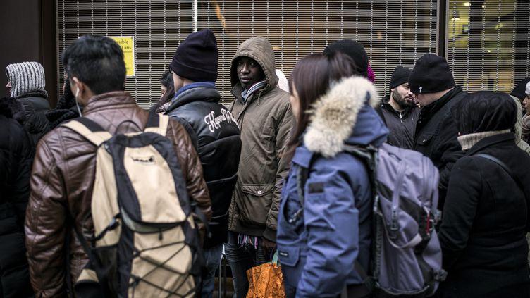 Des étrangers font la queue devant la préfecture de Lyon (Rhône), le 16 février 2015. (JEFF PACHOUD / AFP)
