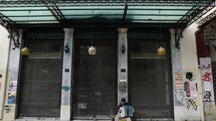 Un musicien joue de l'accordéon devant un magasin fermé à Athènes (Grèce), lundi 30 janvier 2012. (JOHN KOLESIDIS / REUTERS)