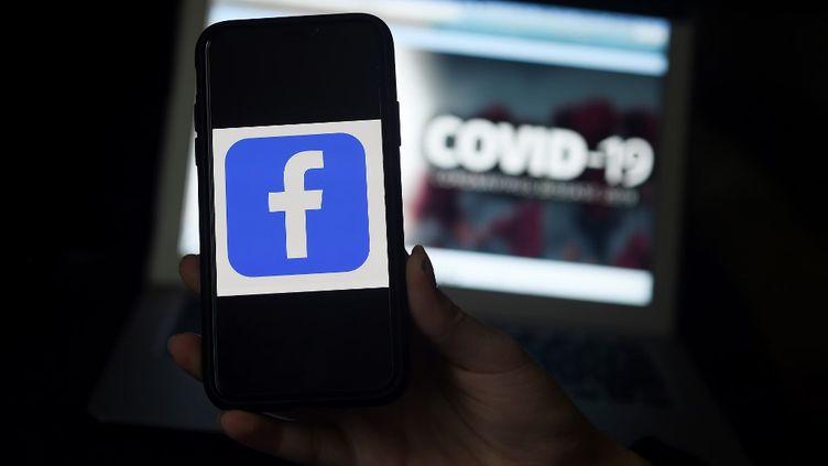 Un téléphone connectée à l'application Facebook photographie un message d'avertissement lié au coronavirus, le 30 mars 2020, à Arlington (Etats-Unis). (OLIVIER DOULIERY / AFP)