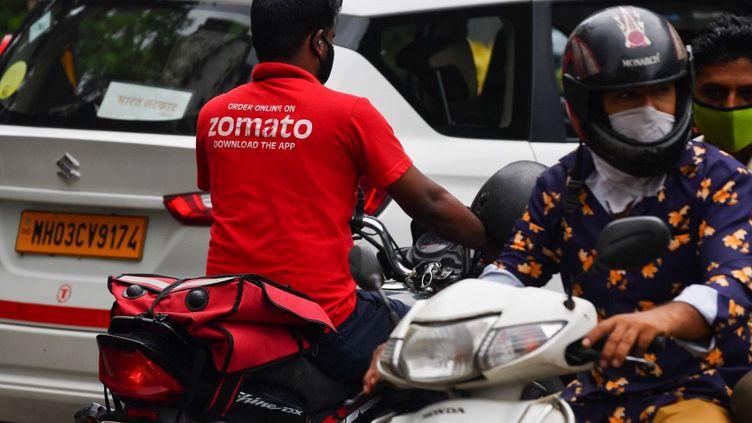 Un livreur travaillant pour Zomato conduit une moto dans une rue de Mumbai, en Inde, le 8 juillet 2021. (INDRANIL MUKHERJEE / AFP)