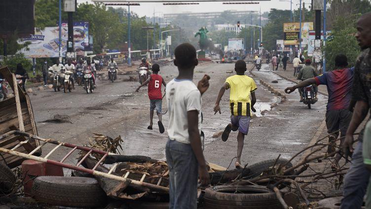 Sur une barricade, un jeune manifestant observent l'arrivée de la police, à Bamako, au Mali, le 11 juillet 2020. (MICHELE CATTANI / AFP)