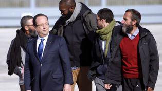 François Hollande avec les quatre ex-otages du Niger,Marc Feret, Thierry Dol, Pierre Legrand and Daniel Larribe, mercredi 30 octobre 2013, sur la base aérienne de Villacoublay. (KENZO TRIBOUILLARD / AFP)