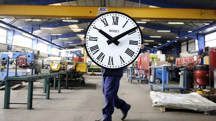 Un employé de l'entreprise Bodet transporte une horloge, le 26 mars 2014, àTrementines (Maine et Loire). (JEAN-SEBASTIEN EVRARD / AFP)