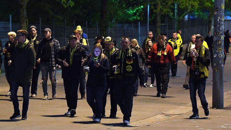 Des supporteurs quittent le stade Signal Iduna Parkaprès le report du quart de finale aller de la Ligue des champions Dortmund-Monaco. Des explosions ont touché le bus du club allemand, le 11 avril 2017. (FEDERICO GAMBARINI / AFP)