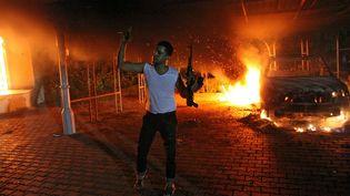 Un homme brandit une arme après l'attaque du consulat américain de Benghazi, en Libye, le 11 septembre 2012. (AFP)