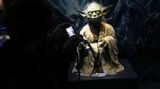 """Un visiteur prend une photo lors de l'exposition """"Star Wars Identities"""" à Vienne (Autriche) le 17 décembre 2015. (LEONHARD FOEGER / REUTERS)"""