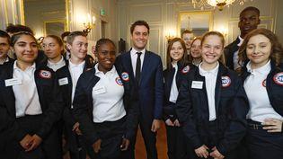 """De jeunes volontaires du """"service national universel"""" entourent le secrétaire d'Etat chargé de la jeunesse, Gabriel Attal. (FRANCOIS GUILLOT / AFP)"""