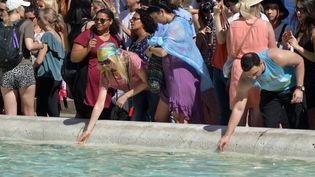 Des touristes se raffraichissent près de la fontaine de Trévi à Romme, en juin 2017. (TIZIANA FABI / AFP)