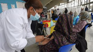 Une femme âgée reçoit une dose du vaccin Pfizer-BioNTechcontre le coronavirusCovid-19, alors que d'autres attendent leur tour dans la salle de sport El-Menzah de Tunis, le 3 mai 2021. (FETHI BELAID / AFP)