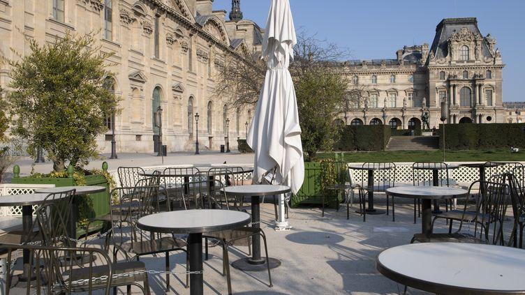Chaises et tables de restaurant, vides, sur la terrasse d'un restaurant du Louvre, à Paris, le 10 avril 2020. (ODILE GINE / AFP)