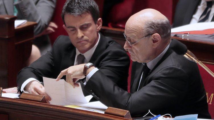 Le Premier ministre, Manuel Valls, échange avec son ministre chargé des Relations avec le Parlement, Jean-Marie Le Guen, le 16 avril 2014, dans l'hémicycle. (JACQUES DEMARTHON / AFP)