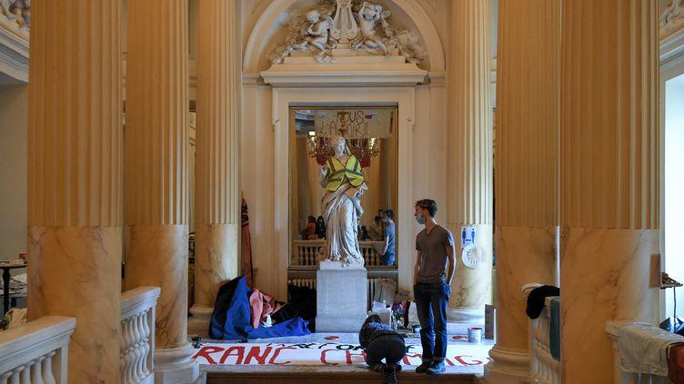 Les manifestants préparent des banderoles alors qu'ils occupent le théâtre de l'Odéon depuis le 4 mars, à Paris, le 25 mars 2021 (ALAIN JOCARD / AFP)