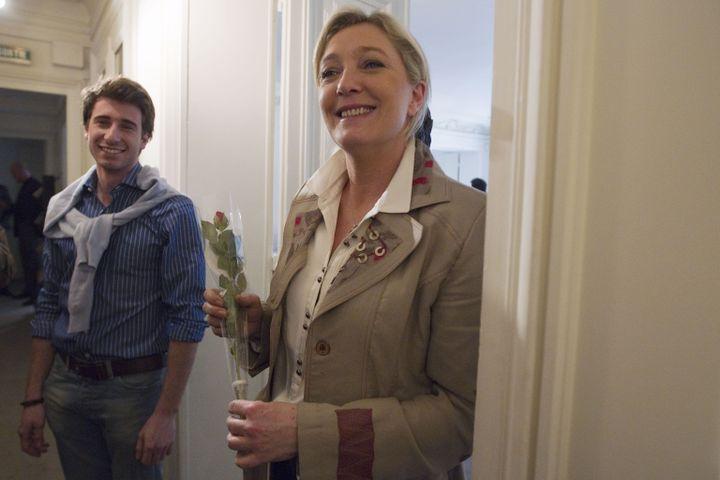 Le président du Front national de la jeunesse, Julien Rochedy, pose avecla candidate à la présidentielle Marine Le Pen au QG du Front national, le 8 mars 2012. (JOEL SAGET / AFP)