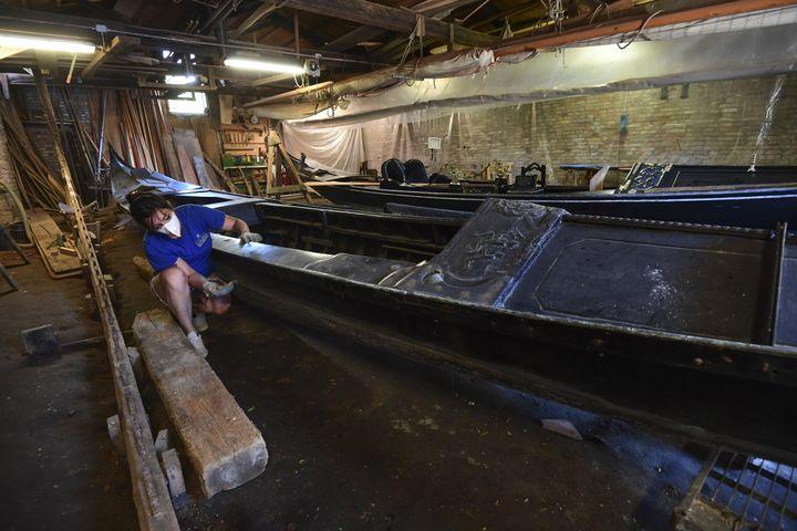 Elisabetta Tramontin réalise les finitions d'une gondole à Venise le 27 mai 2020 (MIGUEL MEDINA / AFP)
