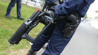Un policier dugroupement d'intervention régionale desHauts-de-Seinetenant un flashball, le 16 juillet 2002 à Nanterre (Hauts-de-Seine). (JACK GUEZ / AFP)