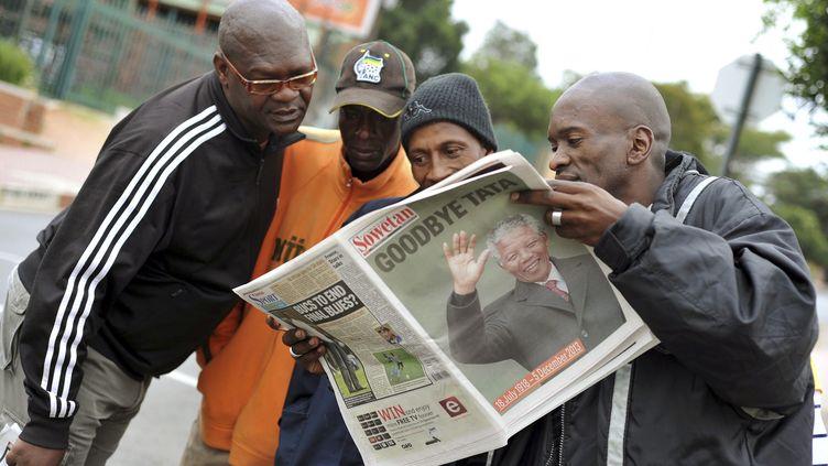 Des habitants de Soweto (Afrique du Sud) lisent un journal consacré à la mort de Mandela, le 6 décembre 2013. (REUTERS)