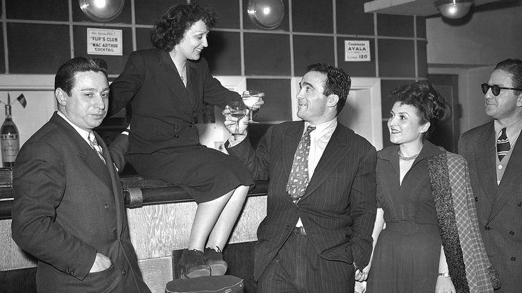 """La chanteuse Edith Piaf et le boxeur Marcel Cerdan trinquent au bar du théâtre du """"Club des Cinq"""", à Paris le 17 mars 1948.  (AFP)"""