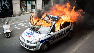 """Une voiture de police brûle le 18 mai 2016 à Paris en marge d'une manifestation des policiers contre """"la haine anti-flic"""". (CITIZENSIDE / NNOMAN CADORET / AFP)"""