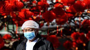Un homme porte un masque de protection dans une rue de Pékin (Chine), jeudi 23 janvier 2020.Le paysa interdit aux trains et aux avions de quitter la ville de Wuhan, au centre d'une épidémie contagieuse qui a fait 17 morts. (NOEL CELIS / AFP)
