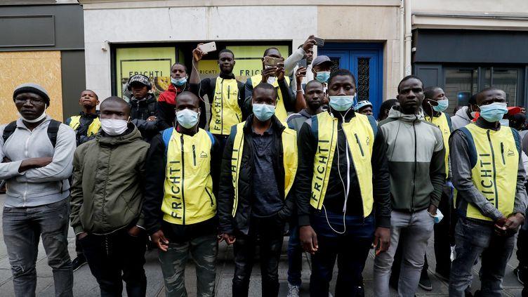 Des travailleurs sans-papiers de la plateforme de livraison de repas Frichti, lors d'une manifestation pour obtenir leur régularisation, le 8 juin 2020 à Paris. (FRANCOIS GUILLOT / AFP)
