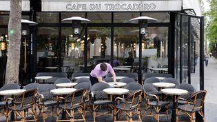 Un serveur nettoie les tables de la terrasse de son café en prévision de la levée des restrictions liées au Covid-19, mardi 11 mai 2021 à Paris. (LUDOVIC MARIN / AFP)