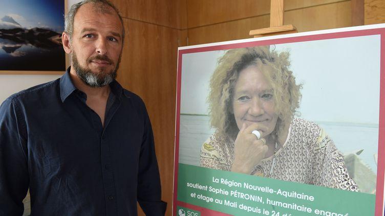 Sébastien Chadaud-Pétronin, devant un portrait de sa mère, enlevée au Mali en 2016. (MEHDI FEDOUACH / AFP)